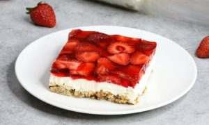 Strawberry Pretzel Salad – A guaranteed hit at any parties! In one bite, you will get the saltiness from its pretzel crust, sweetness from the creamy and smooth cream cheese, and the fresh flavor from the strawberry and jello top layer! So irresistible! Great for holiday and birthday parties. Easy recipe, party desserts. Vegetarian. Video recipe. | Tipbuzz.com