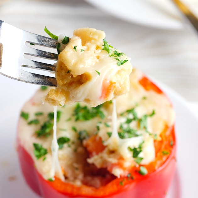 Closeup of a cheese pull on a red stuffed bell pepper with a fork
