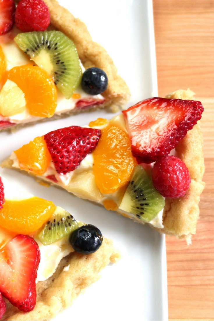 Fruity Pizza - The easiest and most unbelievably beautiful fruit pizza or fruity sugar cookie cake has a soft sugar cookie crust and smooth creamy filling, topped with fresh fruits. All you need is a few simple ingredients: refrigerated sugar cookie dough, cream cheese, sugar, vanilla extract and fruit of your choice! A simple dessert you whole family will be obsessed with. It takes only 20 minutes to make. Perfect for holiday party dessert such as Easter, Mother's Day, Father's Day or birthdays. Quick and easy, vegetarian. Video recipe. | tipbuzz.com