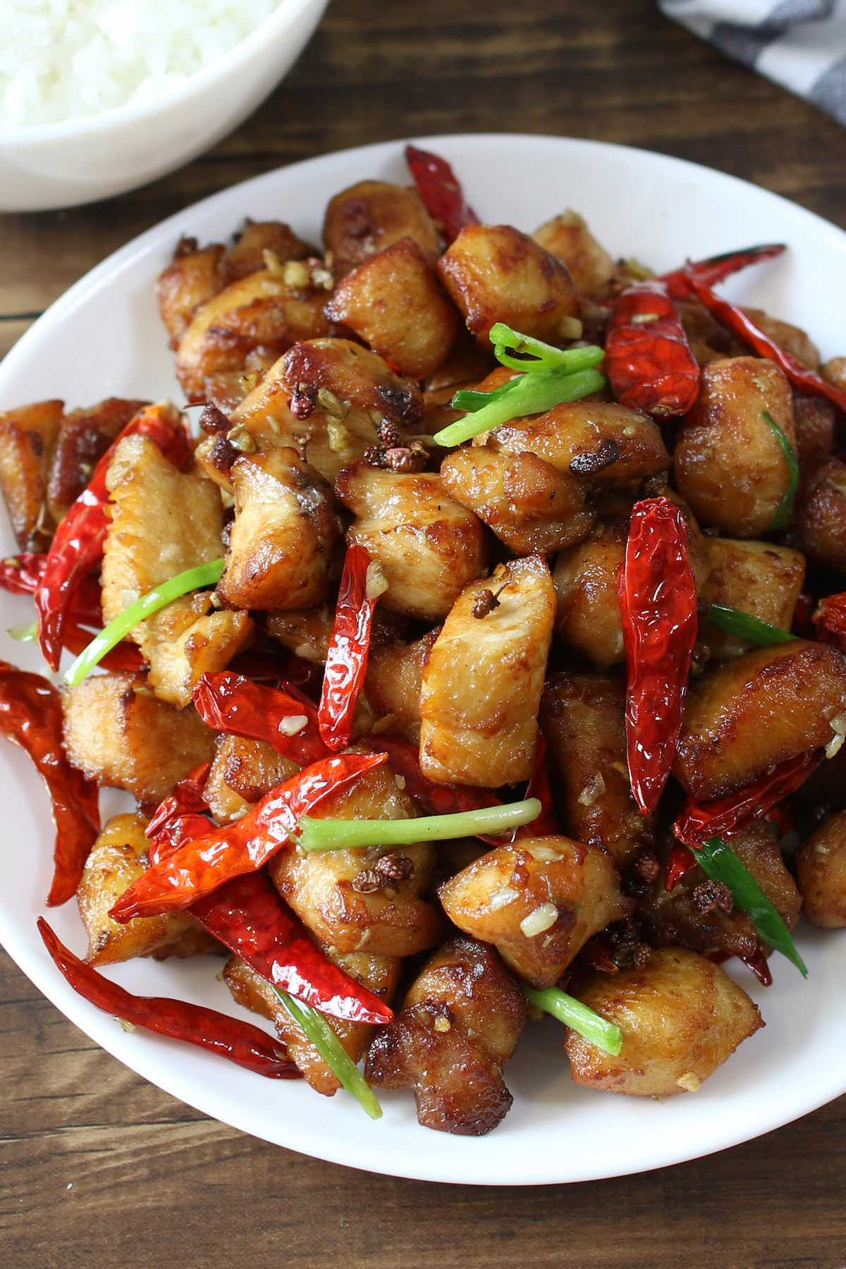 Szechuan chicken cooked with whole Szechuan peppercorns on a serving plate.
