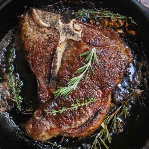 Overhead view of searing a t-bone steak in a very hot cast iron frying pan with the fat sizzling around the meat