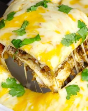 A cheesy Taco Casserole being being served out of a baking dish