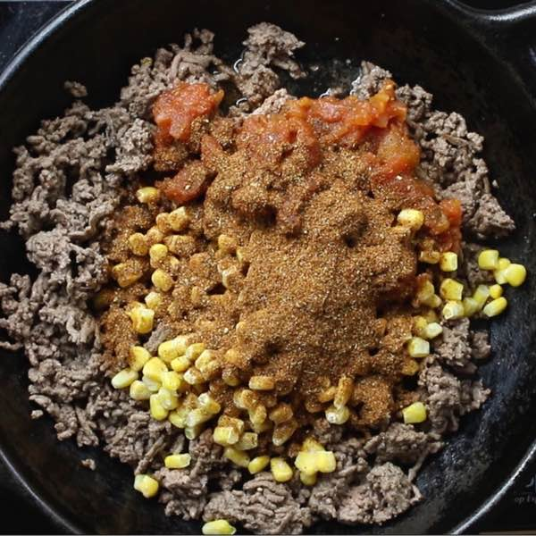 Taco Casserole - this photo shows browned beef in a cast iron skillet with salsa, corn and taco seasoning being added in to make this recipe