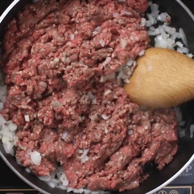 Taco Pasta: frying ground beef with onions and garlic in a large skillet to make an easy dinner