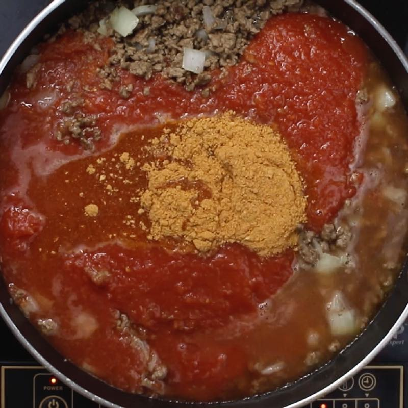 This photo shows combining tomato sauce, taco seasoning and water to with ground beef to make one pot taco pasta