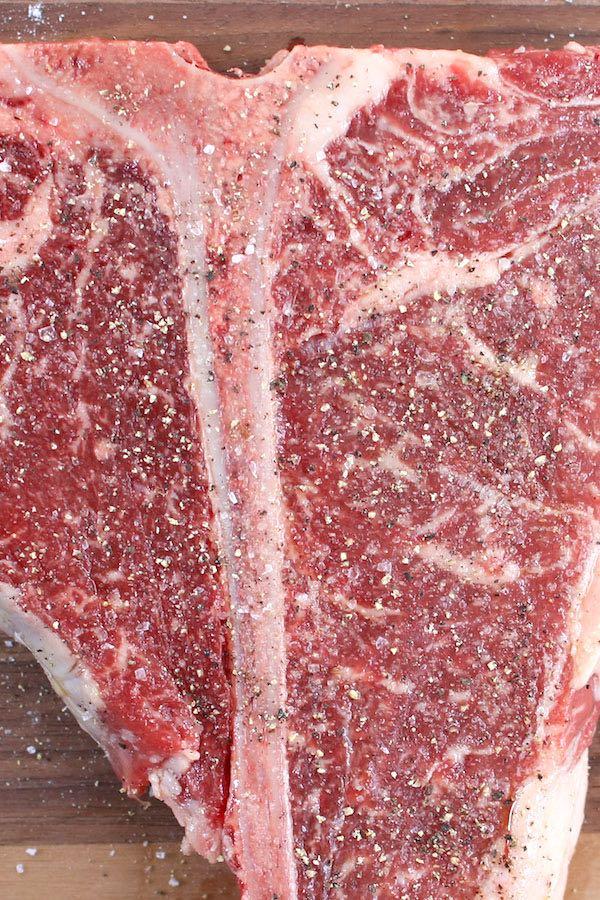 Season T-bone steak with salt and pepper