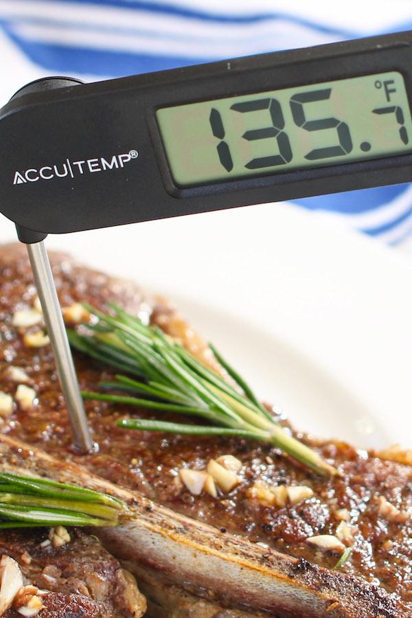 Medium Rare T-bone steak: instant-read thermometer shows 135 F