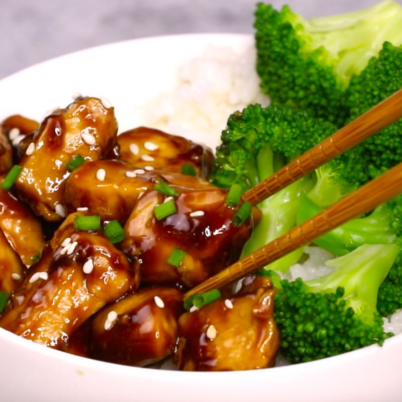 This closeup photo shows chopsticks picking up a piece os delicious Teriyaki Chicken from a rice bowl where it's served with broccoli