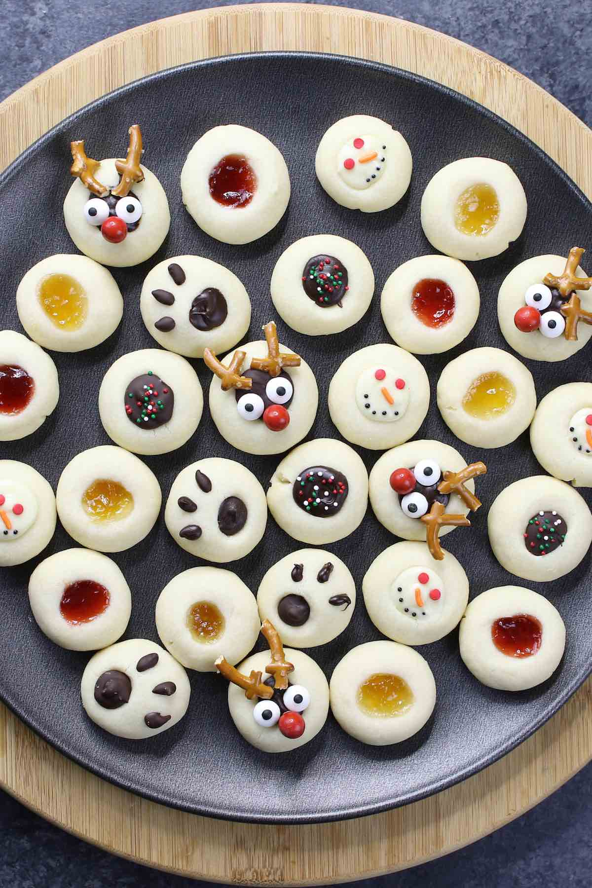 Mixture of jam thumbprint cookies and Christmas chocolate thumbprint cookies on a dark plate.