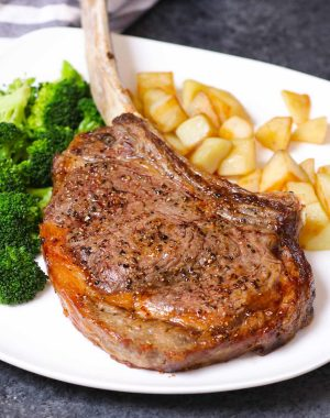 Tomahawk steak on a serving plate with potatoes and broccoli