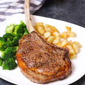 Tomakawk steak on a serving plate with potatoes and broccoli