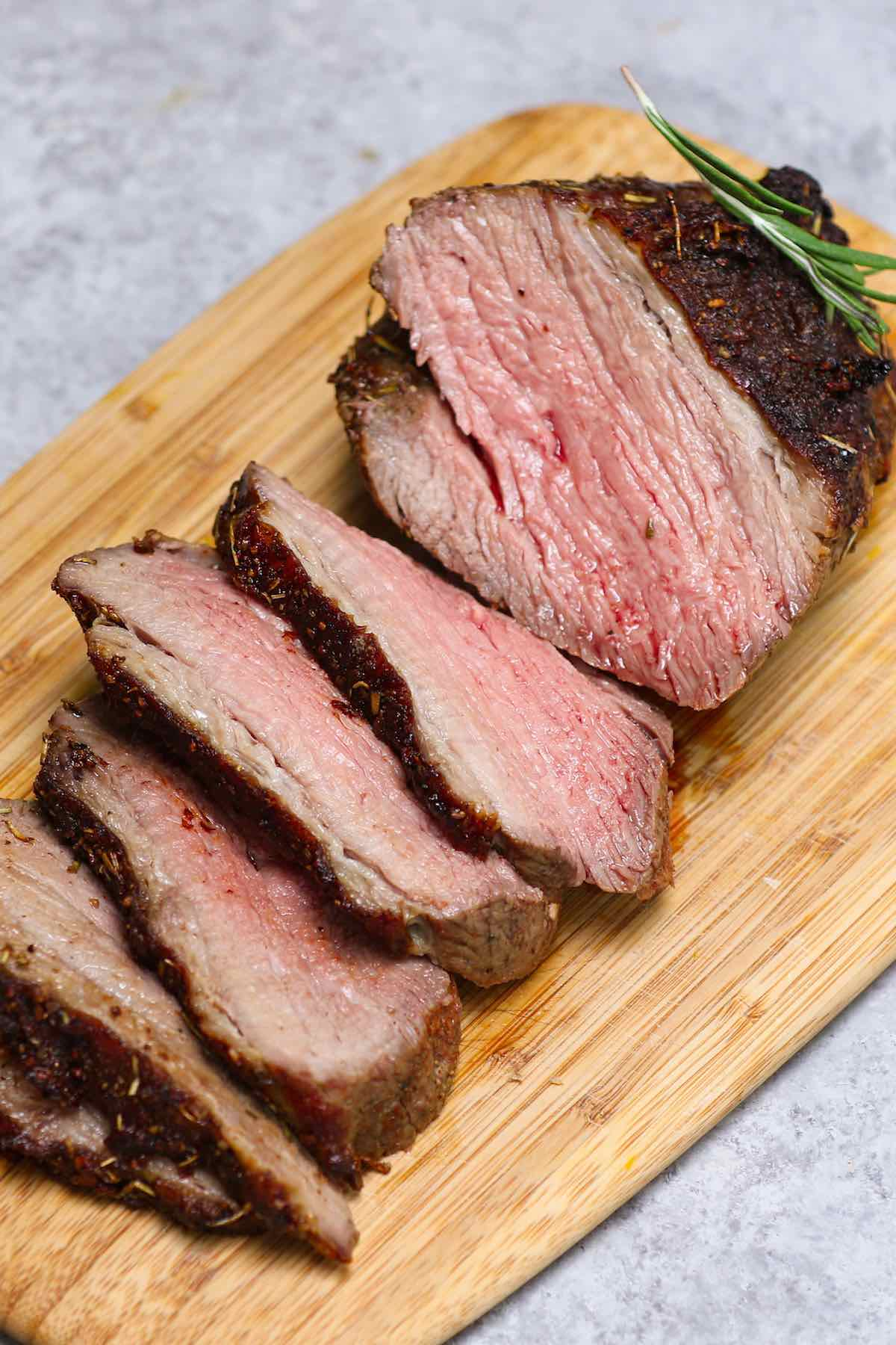Slices of sirloin roast on a carving board showing medium doneness with a pale pink interior