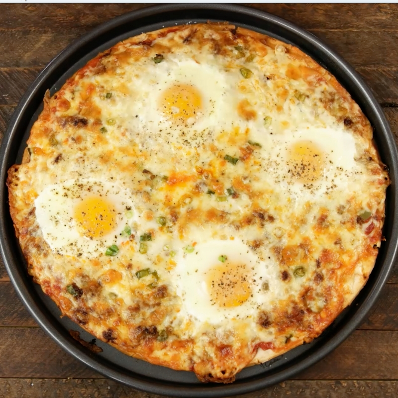 Easy Cheesy Breakfast Pizza With Sausage And Eggs – the easiest and fun breakfast that comes together in no time. All you need is a few simple recipes: your favorite sausage, pizza crust, salsa, green onions, Jack cheese, eggs, salt and pepper. It's the perfect hearty breakfast or brunch recipe to serve to a crowd! Great for a holiday such as Easter, mother's day or father's day brunch. Quick and easy video recipe. | Tipbuzz.com
