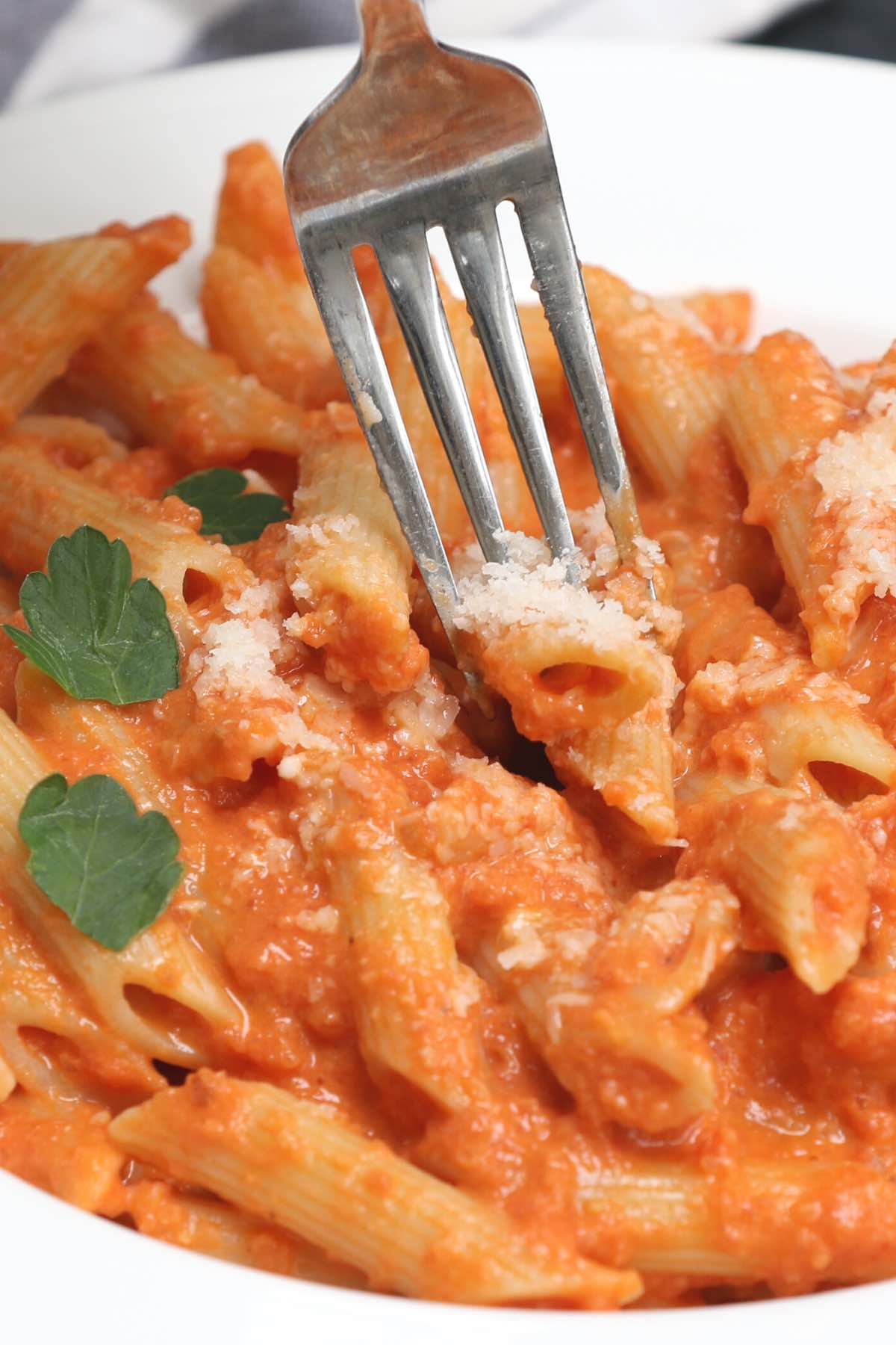 A fork digging into homemade penne alla vodka
