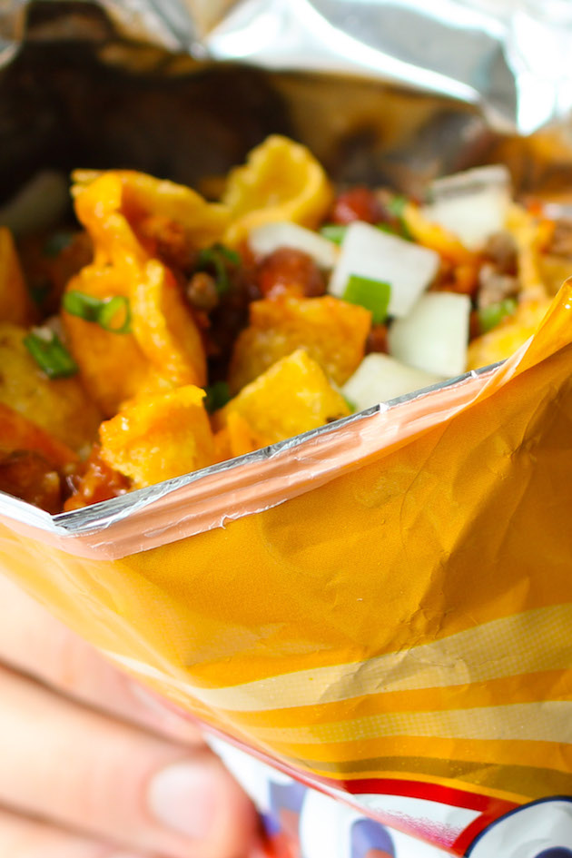 This walking taco recipe features Fritos, ground beef, cheese, onions. This dish is easy to assemble at a party by putting out a walking taco bar