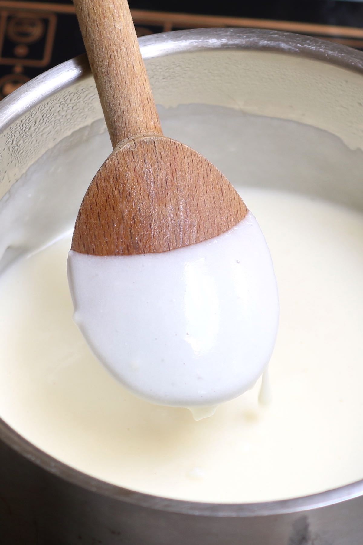 Bechamel sauce coating the back of a wooden spoon once thickened