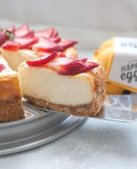 A slice of strawberry white chocolate cheesecake being served