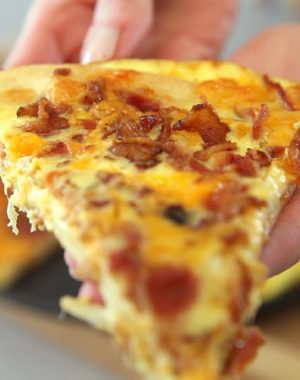 Bacon, Egg & Cheese Breakfast Pizza – you can't resist this delicious breakfast pizza. All you need is a few simple ingredients: pizza dough, cheese, eggs, milk and bacon. Quick and easy breakfast idea. Video recipe. | tipbuzz.com