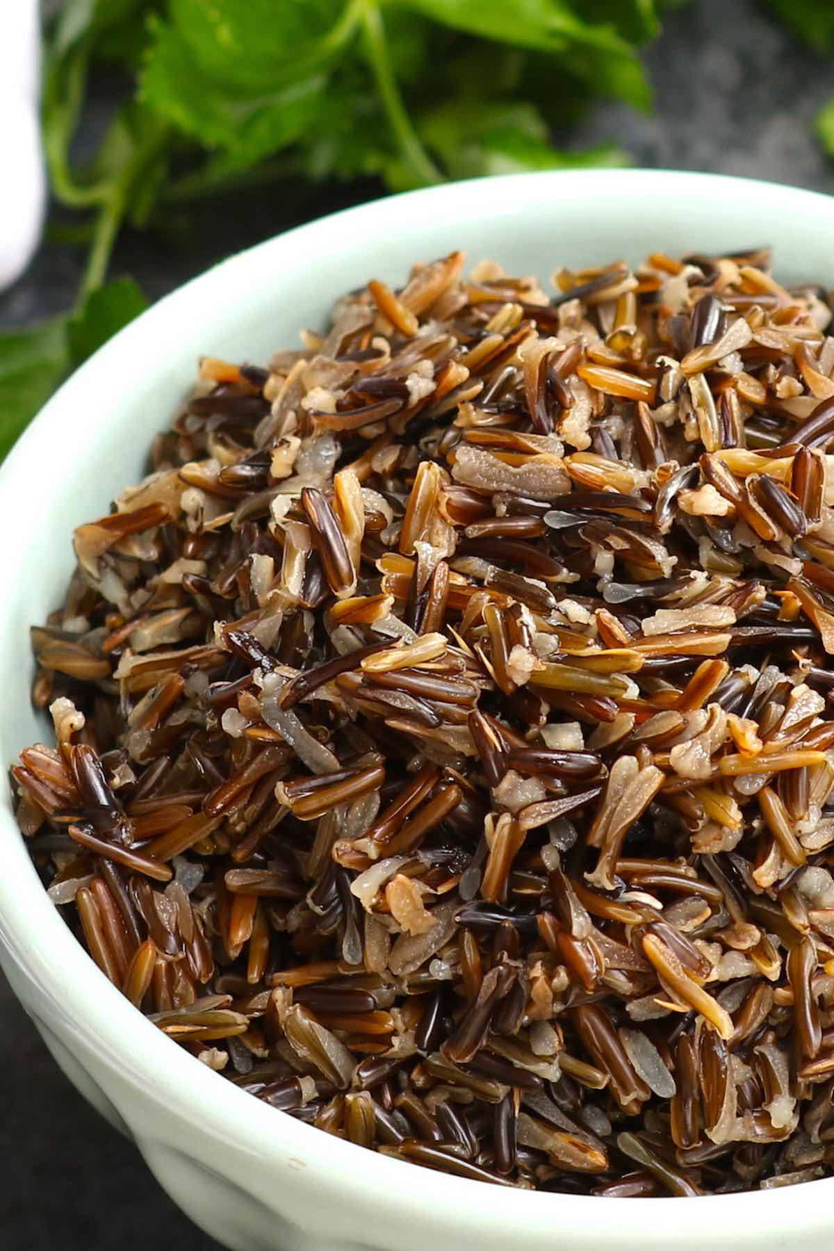 Perfectly cooked wild rice in a serving bowl showing its fluffy, chewy texture and walnut color