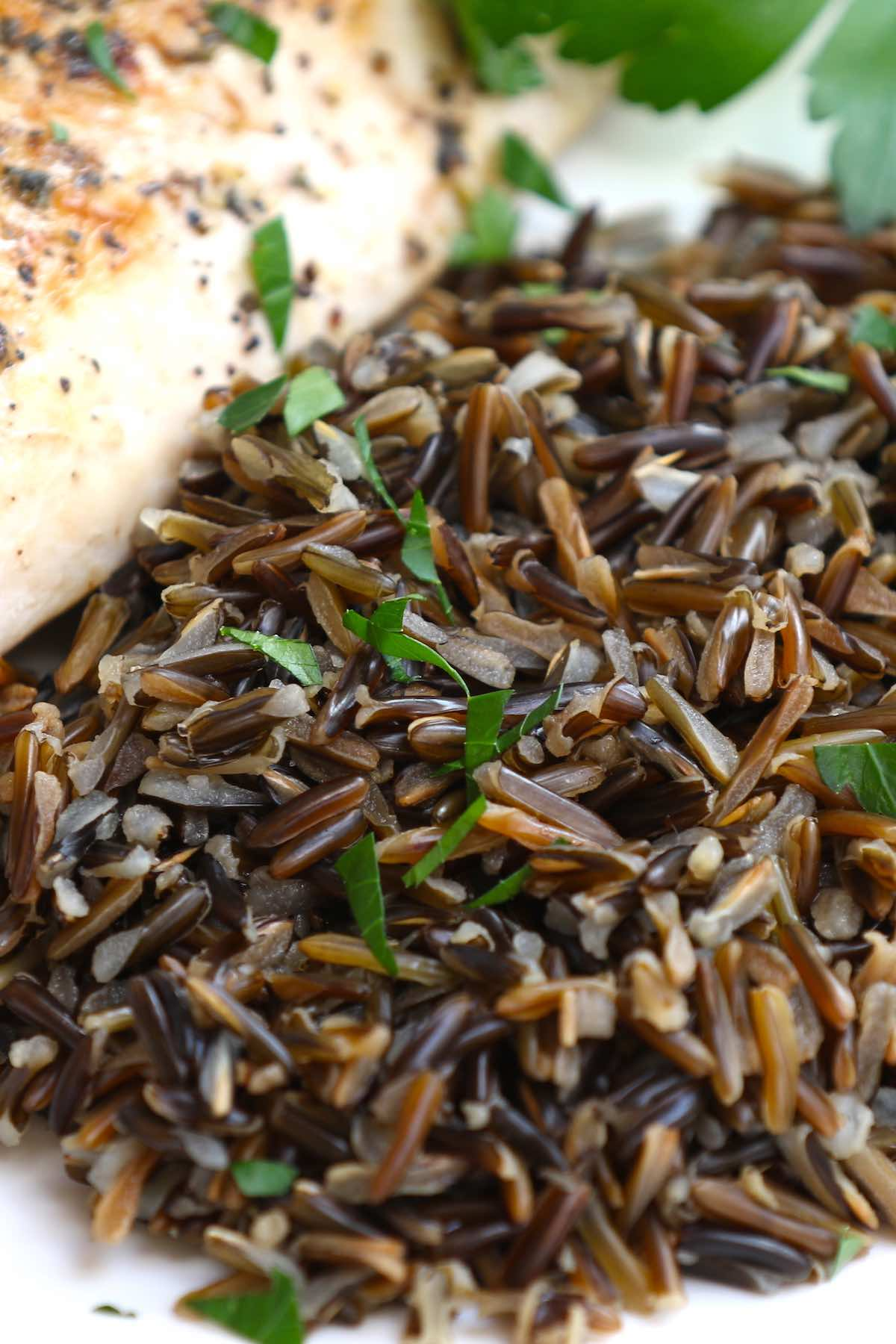 Closeup of wild rice as a side dish for baked chicken breast, all garnished with fresh parsley