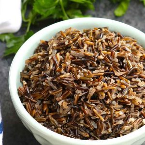 A bowl of fluffy wild rice showing its beautiful fluffy texture and dark brown color