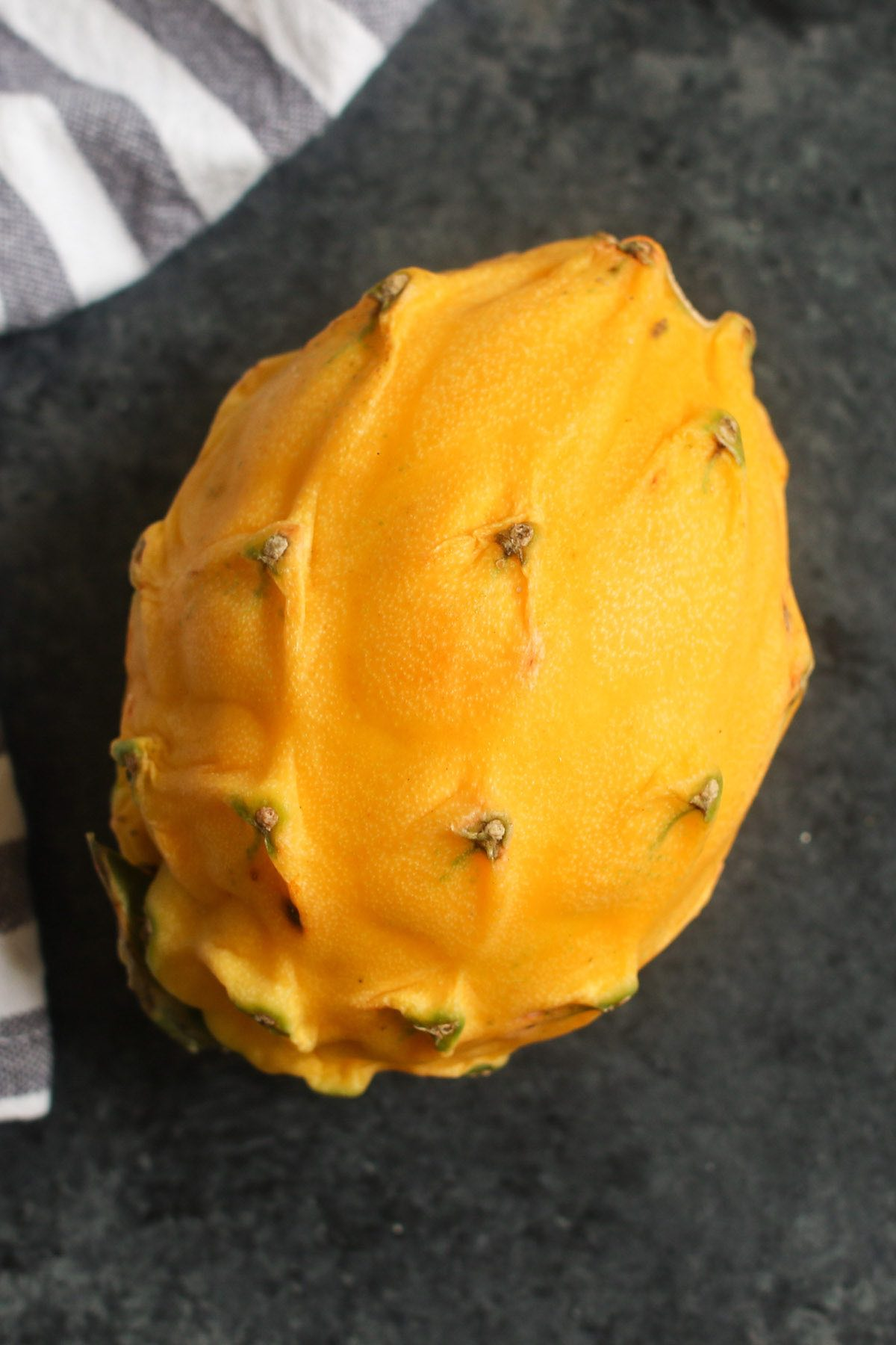 A whole yellow pitaya with its bright yellow color, oblong shape and knobby skin