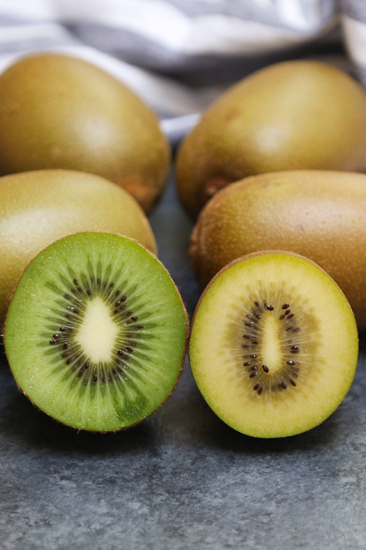 Side-by-side comparison of green kiwifruit and yellow kiwi showing the different colors of the flesh