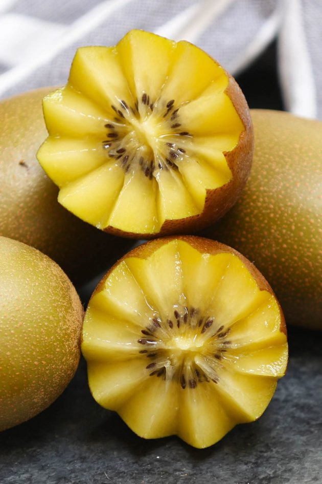 Yellow kiwi cut in a decorative floral pattern showing off its color