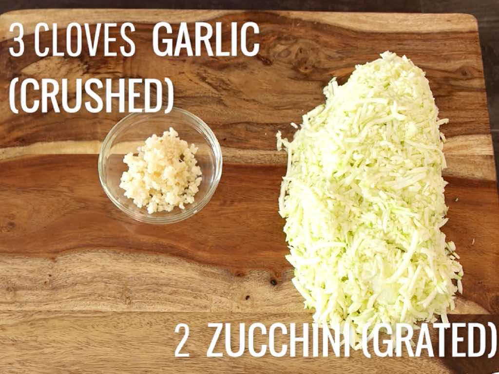 Zucchini Lasagna Roll Ups - this photo show minced garlic and grated zucchini on a cutting board in preparation to make the filling