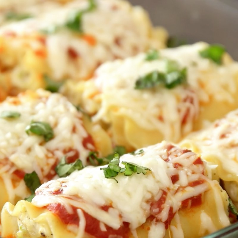 Zucchini Lasagna Roll Ups - this closeup photo shows zucchini lasagna roll ups in a pan ready to serve with chopped fresh basil on top