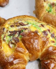 Breakfast Croissant Boats – crispy bacon, fluffy egg and melted cheddar cheese baked in croissant breakfast boats! A quick and easy recipe that's ready in 30 minutes and feeds a crowd! Perfect for breakfast and brunch. So delicious! Video recipe. | Tipbuzz.com