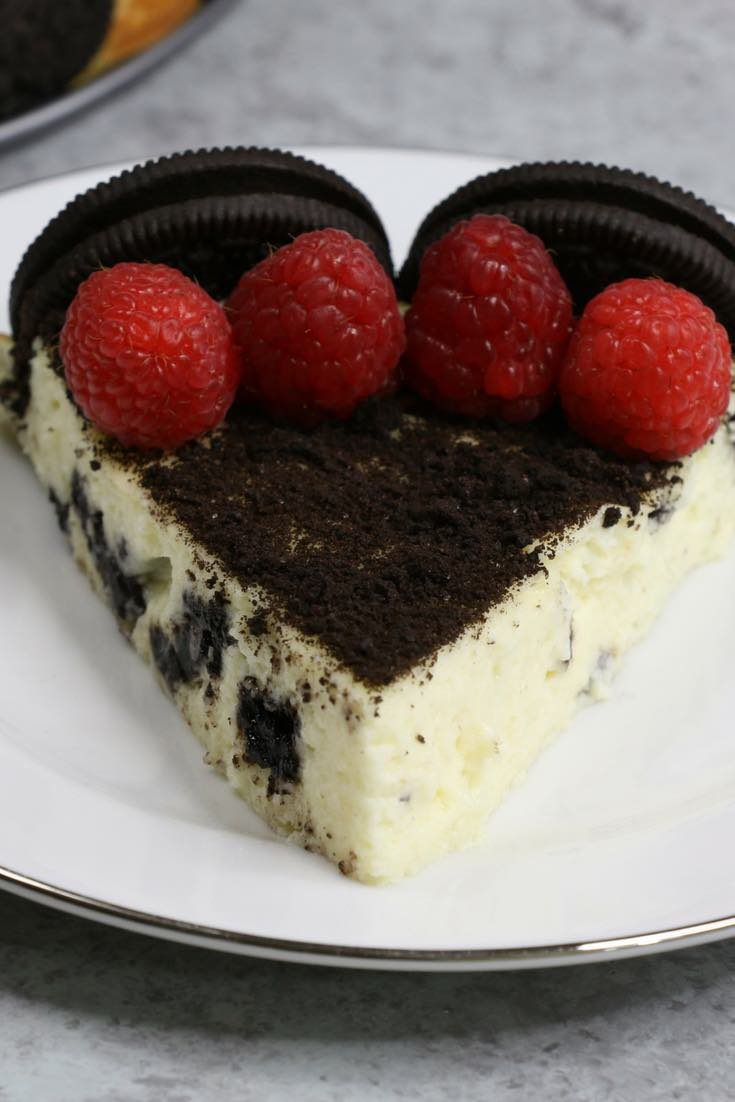 The Ultimate Oreo Cheesecake – the easiest and most beautiful cake topped with cookies and cream crumbs and fresh raspberries. All you need is a few simple ingredients: oreo cookies, cream cheese, sugar, vanilla, eggs, sour cream and raspberries. Great for dessert, brunch, birthday parties or Mother's Day. Video recipe. | tipbuzz.com