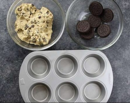 A muffin pan with a bowl of cookie dough and another bowl of oreos