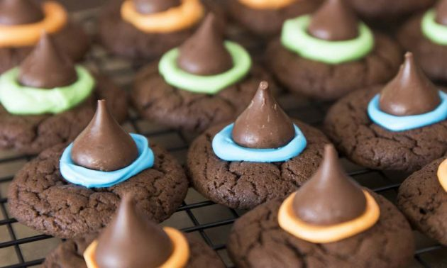 Witch hat cookies on a wire rack with different colors of frosting attaching the Hershey's kisses on top